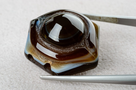 Fine brown and white agate bead held by tweezers. photo