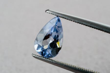 beryl: Fine blue drop shaped blue beryl, aquamarine, gemstone held by tweezers. Stock Photo