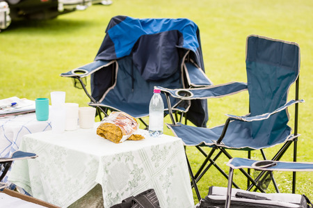 sitt: Empty blue camping seats by table with bottle and bread.