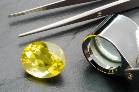 gemology: Yellow lemon quartz gemstone with tweezers and loupe on black stone plate. Stock Photo