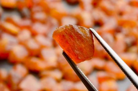 gemological: Pile of brightly orange, uncut spessartite or spessartine garnets with tweezers on black stone plate. Stock Photo