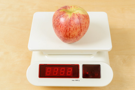 red gram: Red and green apple on white digital scale.