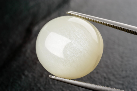 cabochon: Albite gemstone in round cabochon form held by tweezers. Stock Photo