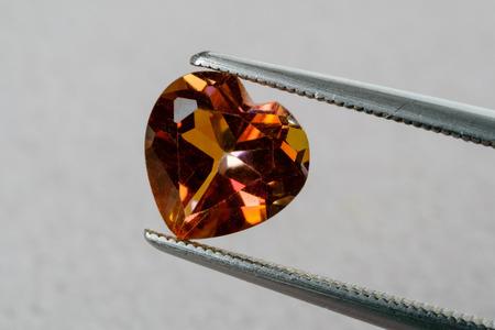 topaz: Heart shaped orange topaz gemstone held by tweezers.