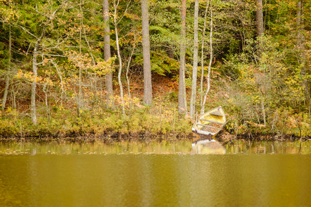 lost lake: Small boat on shore by autumn lake in forest.