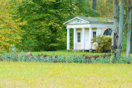 lavish: JOHANNISHUS, SWEDEN - OCTOBER 18, 2014: A lavish playhouse or cabin with pillars. House is placed near forest at the end of a field. Autumn colors all around.
