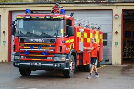 camion de bomberos: Ronneby, Suecia - 26 de octubre 2014: Bombero en pantalones cortos y camiseta a pie de camión de bomberos fuera del edificio de la estación. Truck es de color rojo y amarillo Scania 114G. Editorial