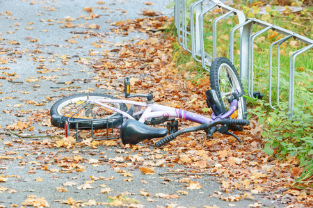 left behind: Ronneby, Sweden - October 26, 2014: Greenfield bicycle for child lying on ground by rack in autumn. Bike could be stolen or forgotten and simply left behind.