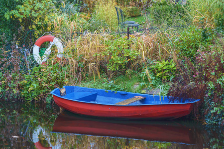 the next life: Colorful blue and red boat at riverside with lush garden in background. Red and white life buoy next to boat. Very calm water and two chairs in garden. Editorial