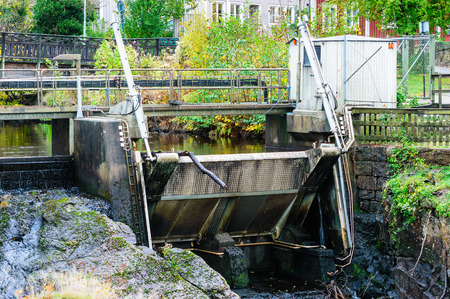 diverted: Closed floodgate at small power station. River is stoped from overflowing and only very little water get through. This way all the flowing water is diverted to the intake to the power station. Stock Photo