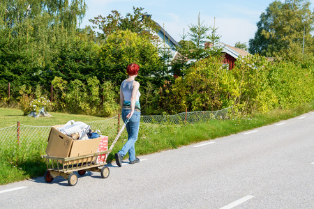 Johannishus, Sweden - September 06, 2014: Female walking along rural street with trolly full of garbage. Warm and sunny day with garden in background. Woman has back towards camera and walk away.