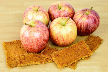 tucker: Natural fresh apples together with tasty dehydrated apple leather on wooden table. Dry fruit leather is a perfect bush tucker or bush food when on a hike.