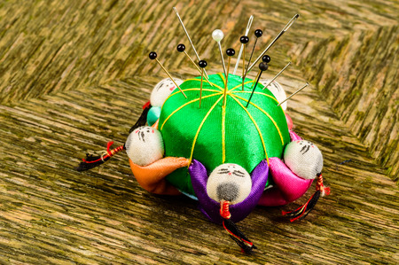 pinhead: Green pincushion with pins and needles. Chinese figures holding cushion in a ring. Painted faces and colorful dresses. Stock Photo