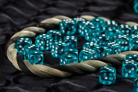 twined: Lots of blue transparent plastic dices on black fabric. Twined silver metal necklace framing dices.