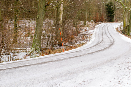 Small country road with snow and tire tracks in winter. Forest in background and orange snow pins at road side. photo