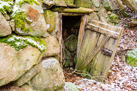 Old abandoned root cellar or underground storehouse with open door in winter. photo