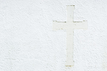Embossed christian cross on church stone wall in white. Cross to the right in picture and place for text to the left.