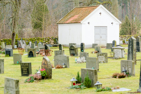 life after death: JOHANNISHUS, SWEDEN - FEBRUARY 14, 2015: Small white building on semetary. Grave stones in foreground. Editorial