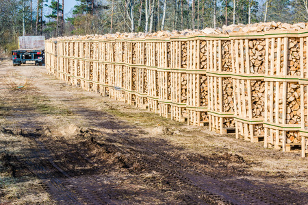 co2 neutral: Solid biofuel as fire wood made of birch, stacked on pallets in outdoor stock. Dirt road in foreground and trailer at the end of stacks. Stock Photo