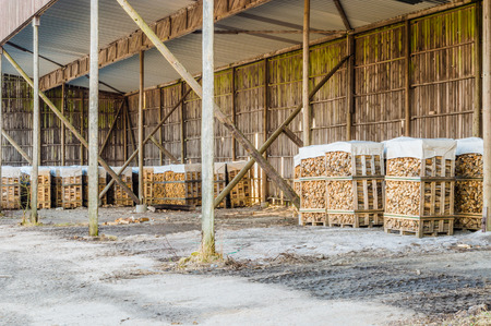 co2 neutral: Fire wood made of birch in outdoor storage under roof. Woden pillars support the roof.