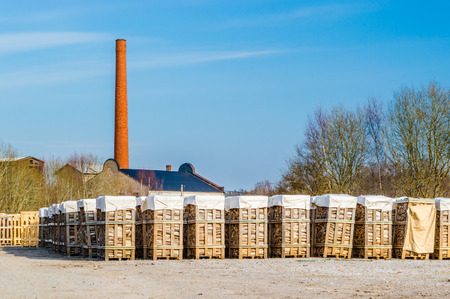 co2 neutral: Biofuel as stacked birch wood on pallets. Smoke stack and roof of factory in background. Blue sky and some trees behind fuel.