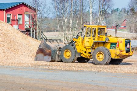 cargador frontal: Cargador frontal amarillo con el cubo en el suelo sacando astillas de madera para biocombustible. Vista desde el lado con el mont�n de astillas de madera y parte de la casa roja en el fondo. Principios de la primavera.