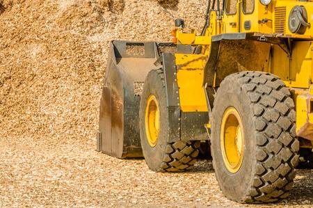 cargador frontal: Cargador frontal amarillo con el cubo en el suelo sacando astillas de madera para biocombustible. Vista desde la izquierda detr�s del veh�culo con pila en frente de ella.