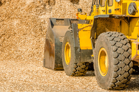 power equipment: Yellow front loader with bucket down scooping wood chips for biofuel. View from left behind vehicle with pile in front of it.