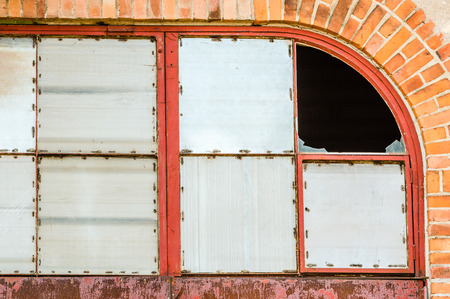 to conceal: Windows covered with metal on red brick wall. One corner window is broken with glass still present. Darkness inside building. Stock Photo
