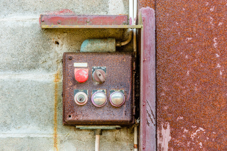 oxidize: Red and rusty old electrical control station with key hole and buttons. Red emergency stop button in upper right corner. Rusty old metal door to the right. Grey brick wall to the left. Stock Photo