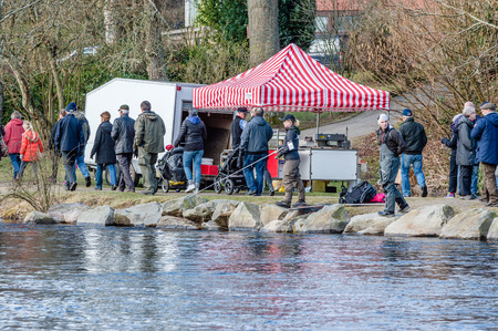 fish vendor: MORRUM, SWEDEN - MARCH 28, 2015: Premiere day for trout and salmon fishing. Spectators look and walk by while people fish. Female fishing from stony riverside. Vendor behind her.