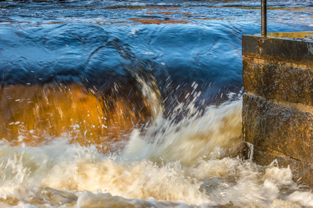 rushes: Wild river rushes by a stone construction with metal top. Waterlevels are high with large water volume. Stock Photo