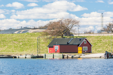 standby: KUNGSHOLMEN, SWEDEN - APRIL 3, 2015: A small ferry station to military facility in the archipelago. Concrete bunker and green grass in background. No boats or people. Clouds in sky, sunshine.