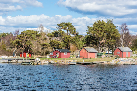 fishing cabin: TJURKO, SWEDEN - APRIL 3, 2015: Three unknown senior persons sitting outside small fishing cabin near the sea and sunbathing. Spring is arriving and people enjoy it. Editorial