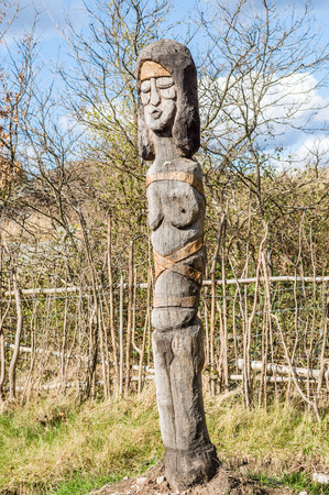 the  fertility: SENOREN, SWEDEN - APRIL 3, 2015: Fertility totem statue of woman carved by hand and made of oak. Part of viking age village replica in southern Sweden in early spring. Editorial