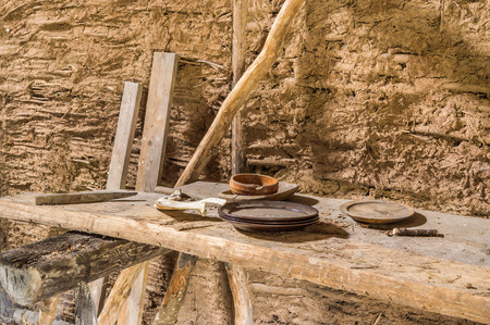 replica: Part of viking age village replica in southern Sweden in early spring. Left behind wooden plates and a jaw bone of a pig on rough table. Stock Photo