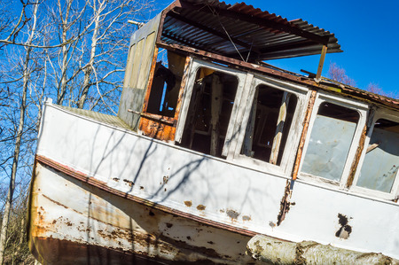 pulled over: Old shipwreck of passanger boat all the way up into the forest where it has been pulled to its final resting place. Nature is closing in with trees and broken branches all over. Blue sky and sunshine. Stearing cabin up close. Stock Photo