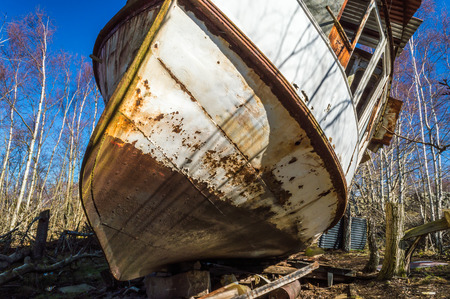 oxidize: Old shipwreck of passanger boat all the way up into the forest where it has been pulled to its final resting place. Nature is closing in with trees and broken branches all over. Blue sky and sunshine. Stock Photo
