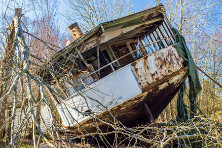 pulled over: Stern of old shipwrecked passanger boat all the way up into the forest where it has been pulled to its final resting place. Nature is closing in with trees and broken branches all over. Blue sky and sunshine.