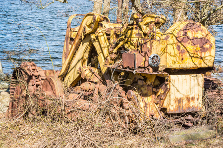 Abandoned and weathered yellow bulldozer crawler. Nature is trying to cover it with vegetation. Sea in background. Lots of rust and metal. photo