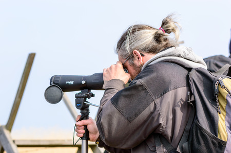 birdwatcher: Bejershamn, Sweden - April 25, 2015: Unknown male birdwatcher using spotting scope to find interesting birds to watch. Person seen from side and behind from waist up. Bejershamn is a protected wildlife reserve known for its birdlife.