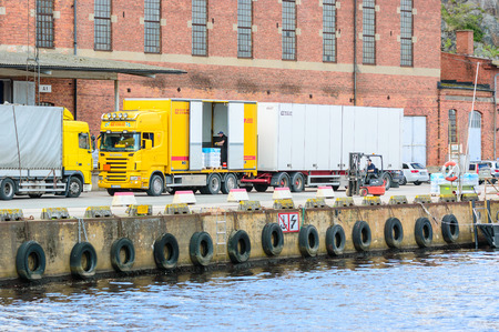 unload: Karlshamn Sweden  May 06 2015: Two unknown male worker unload a truck at the docks outside an old factory building. One is driving a forklift the other is inside truck.