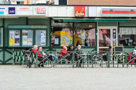 fenced in: Karlshamn Sweden  May 06 2015: Senior persons sitting outside with gloomy faces and relaxing. Shops in background. Fenced in area around persons.