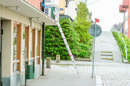 unattended: Karlshamn Sweden  May 06 2015: Unattended ladder placed on sidewalk against building. Air conditioner being fitted. Nobody in sight.