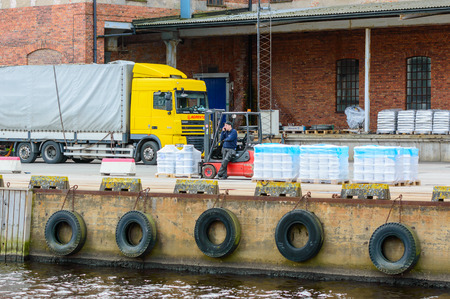 phonecall: Karlshamn Sweden  May 06 2015: Unknown male forklift driver making a phonecall while unloading pallets at the docks. Truck and building in background. Editorial