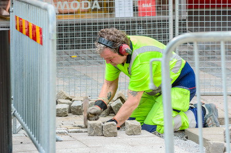 fenced in: Karlshamn Sweden  May 06 2015: Unknown male paver at work with setting granite stones in public street. He is working within a fenced area outside shops.