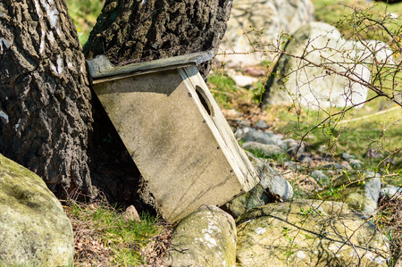 shrubbery: Weathered nesting box for waterfowl that has fallen down from a tree. Shrubbery and granite stones on the ground. Stock Photo