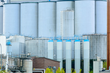 gigantic: Gigantic silos on an industrial site. All are grey and some have blue tops. Almost form a solid background of metal.