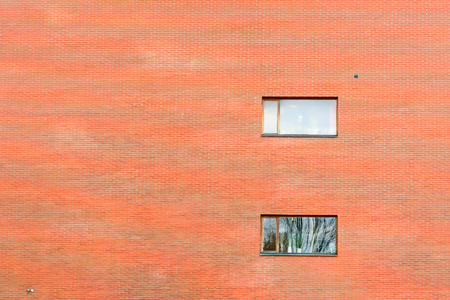 Huge brick wall on modern building with two windows. Reflections in windows. Copy space to the left. photo