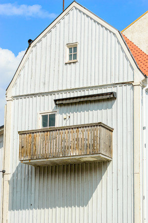 unpainted: Unpainted old balcony on grey wooden house with small windows. Stock Photo